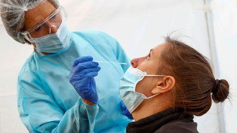 Kaitserõivastes tervishoiutöötaja koroonaproovi võtmas