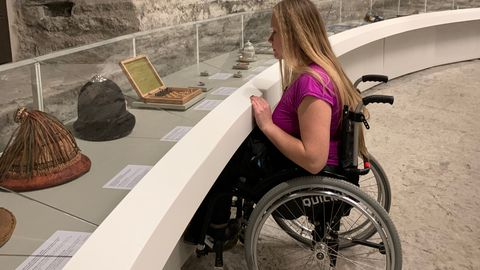 Helen Bokmann ratastoolile mõeldud vitriini juures.